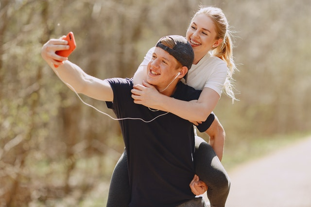 A picture of a guy carrying a lady and taking a selfie with his smartphone. They are both smiling.
