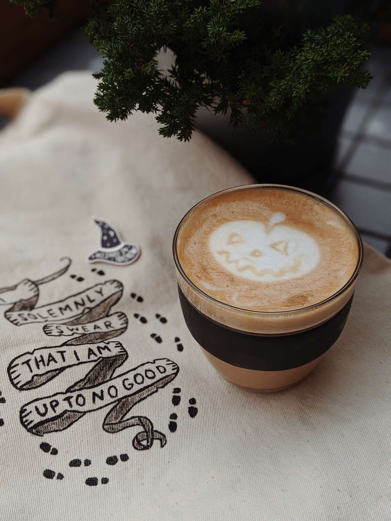 A cup containing coffee with Halloween design