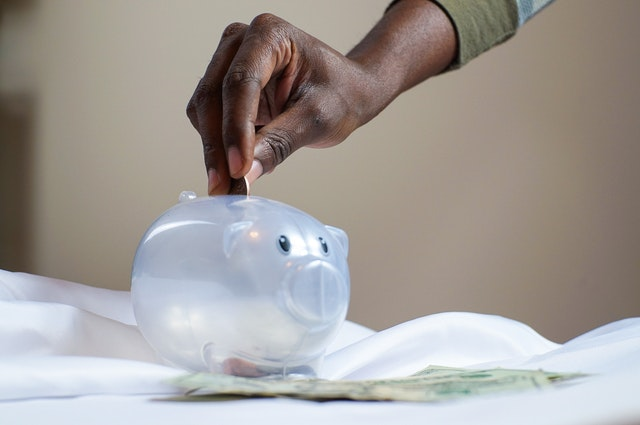 A man saving money in a piggy bank for investing