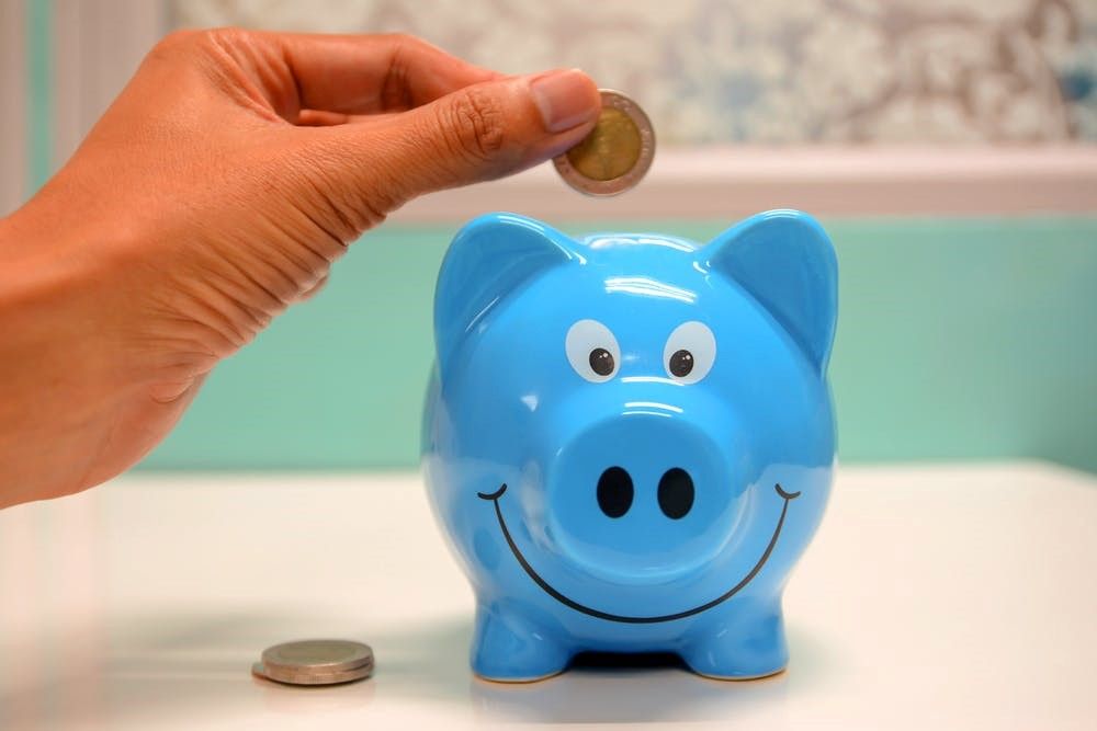 An image of a person saving in a piggy banking in a