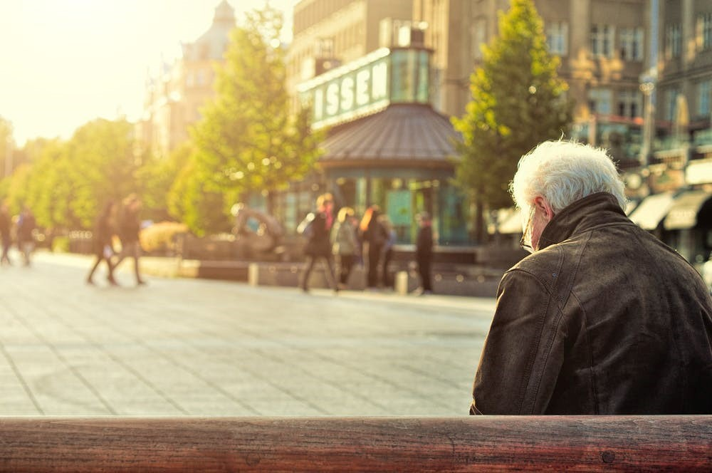 A retired old man sitting on a park bench.