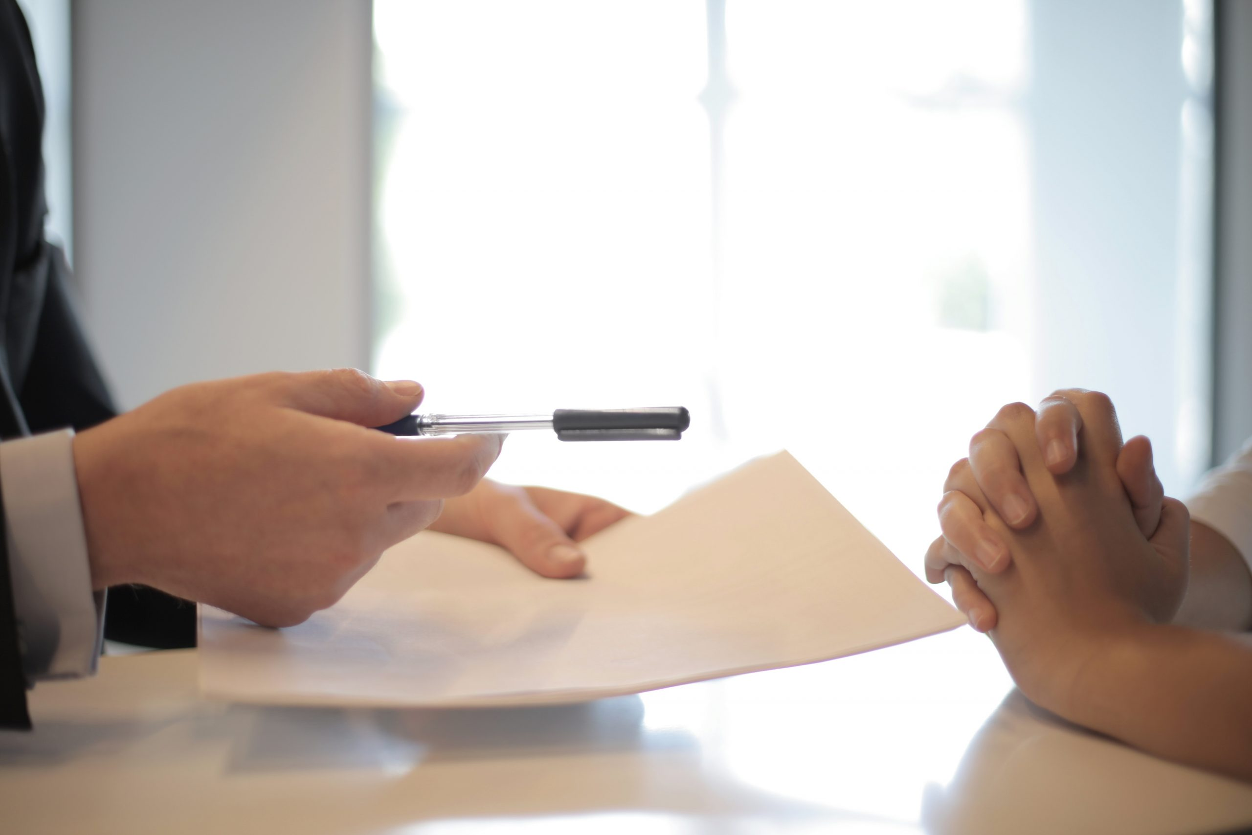 Two people handling a contract with a pen