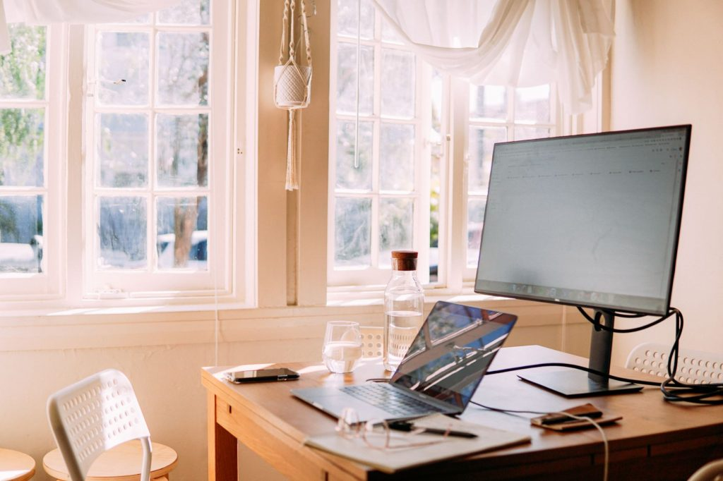 Home office containing a laptop and screen with book and pen